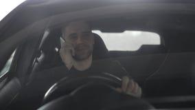 Ελκυστικός ευτυχής επιχειρηματίας που κουβεντιάζει το έξυπνο τηλέφωνο καθμένος μέσα στο αυτοκίνητό του υπαίθρια Στοκ Φωτογραφίες