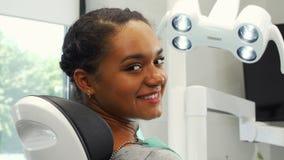 Ελκυστικός θηλυκός ασθενής που χαμογελά στη συνεδρίαση καμερών σε μια οδοντική καρέκλα απόθεμα βίντεο