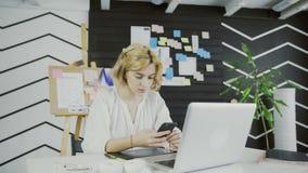Ελκυστικός θηλυκός σχεδιαστής που χρησιμοποιεί το έξυπνο τηλέφωνο στο γραφείο απόθεμα βίντεο