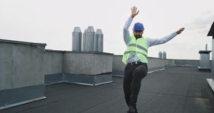 Ελκυστικός και συγκινημένος νέος μηχανικός ή αρχιτέκτονας στη στέγη του εργοτάξιου που χορεύει και που κινείται χαρισματική μέσα απόθεμα βίντεο