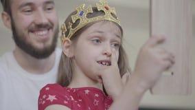 Ελκυστικός νέος γενειοφόρος πατέρας πορτρέτου που βάζει την κορώνα στο κεφάλι του μικρού κοριτσιού του, που κάνει την πριγκήπισσά απόθεμα βίντεο