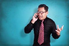 Ελκυστικός νέος επιχειρηματίας που μιλά στο τηλέφωνό του, που συγκλονίζεται cryin Στοκ Εικόνες