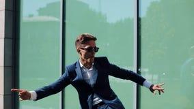 Ελκυστικός νέος επιχειρηματίας που χορεύει στο επίτευγμα και την επιτυχία εορτασμού οδών σε σε αργή κίνηση έξω από το γραφείο του απόθεμα βίντεο