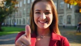 Ελκυστικός νέος θηλυκός παρουσιάζοντας αντίχειρας επάνω, ευτυχής και θετικός, έξω από το πανεπιστήμιο, σε μια ηλιόλουστη ημέρα φιλμ μικρού μήκους