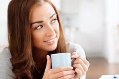 Ελκυστικός νέος καφές κατανάλωσης γυναικών στο σπίτι Στοκ Φωτογραφίες