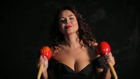 Ελκυστικός νέος μουσικός brunette που παίζει τα κόκκινα maracas απόθεμα βίντεο
