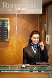 Ελκυστικός νέος ρεσεψιονίστ που λαμβάνει τις κλήσεις Στοκ Εικόνες