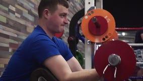 Ελκυστικός νεαρός άνδρας που κάνει bicep τις μπούκλες σε μια μηχανή στη γυμναστική Να εργαστεί πραγματικά σκληρά φιλμ μικρού μήκους