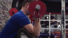 Ελκυστικός νεαρός άνδρας που κάνει bicep τις μπούκλες σε μια μηχανή στη γυμναστική Να εργαστεί πραγματικά σκληρά απόθεμα βίντεο