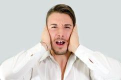 Ελκυστικός νεαρός άνδρας που καλύπτει τα αυτιά του, που ενοχλούνται Στοκ Φωτογραφίες