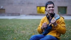 Ελκυστικός νεαρός άνδρας που παίζει μια συνεδρίαση ukulele στη χλόη φιλμ μικρού μήκους