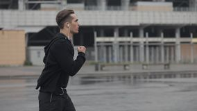 Ελκυστικός νεαρός άνδρας που τρέχει υπαίθρια να φορέσει τα ακουστικά σε αργή κίνηση Βροχερός καιρός Καρδιο άσκηση workout : φιλμ μικρού μήκους