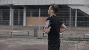 Ελκυστικός νεαρός άνδρας που τρέχει υπαίθρια να φορέσει τα ακουστικά σε αργή κίνηση Βροχερός καιρός Καρδιο άσκηση workout : απόθεμα βίντεο