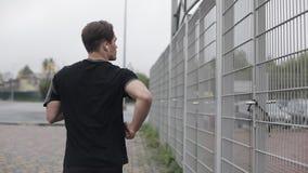 Ελκυστικός νεαρός άνδρας που τρέχει υπαίθρια να φορέσει τα ακουστικά σε αργή κίνηση Βροχερός καιρός E Καρδιο άσκηση απόθεμα βίντεο
