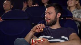 Ελκυστικός νεαρός άνδρας που τρώει popcorn κατά τη διάρκεια του τρυπώντας κινηματογράφου στον κινηματογράφο απόθεμα βίντεο