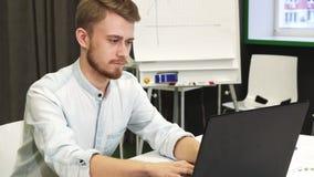 Ελκυστικός νεαρός άνδρας που χρησιμοποιεί το έξυπνα τηλέφωνο και το lap-top του στο γραφείο απόθεμα βίντεο