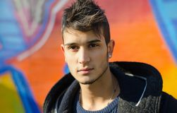 Ελκυστικός νεαρός άνδρας ενάντια στα ζωηρόχρωμα γκράφιτι Στοκ εικόνες με δικαίωμα ελεύθερης χρήσης