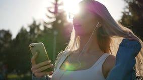 Ελκυστικός ξανθός πνίγει τη μουσική στο smartphone της υπαίθρια Γυναίκα που απολαμβάνει τη μουσική στο ηλιοβασίλεμα o φιλμ μικρού μήκους