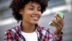 Ελκυστικός σγουρός μαλλιαρός σπουδαστής που φαίνεται διαθέσιμος καθρέφτης χεριών, που απολαμβάνει την εμφάνισή της στοκ εικόνες με δικαίωμα ελεύθερης χρήσης