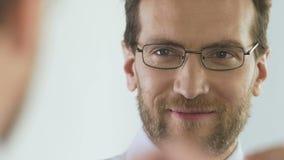 Ελκυστικός τραπεζίτης που φορά eyeglasses και που κοιτάζει στον καθρέφτη, καλή διάθεση απόθεμα βίντεο