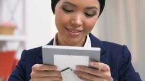 Ελκυστικός υπάλληλος γραφείων θηλυκών που εξετάζει τη φωτογραφία στο πλαίσιο, ελλείπον σπίτι, σπάσιμο απόθεμα βίντεο
