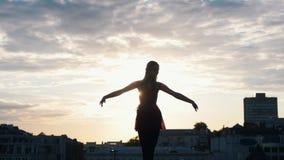 Ελκυστικός χορευτής μπαλέτου γυναικών που κάνει τις ασκήσεις μπαλέτου στον υπαίθριο ενώ ηλιοβασίλεμα απόθεμα βίντεο