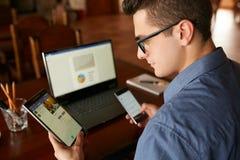 Ελκυστικό άτομο στα γυαλιά που λειτουργούν με τις πολλαπλάσιες ηλεκτρονικές συσκευές Διαδικτύου Ο επιχειρηματίας Freelancer έχει  Στοκ φωτογραφίες με δικαίωμα ελεύθερης χρήσης