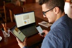Ελκυστικό άτομο στα γυαλιά που λειτουργούν με τις πολλαπλάσιες ηλεκτρονικές συσκευές Διαδικτύου Ο επιχειρηματίας Freelancer έχει  Στοκ Φωτογραφία