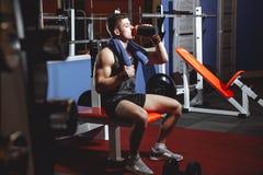 Ελκυστικό αθλητικό άτομο που στηρίζεται μετά από να εκπαιδεύσει στη γυμναστική στοκ φωτογραφίες