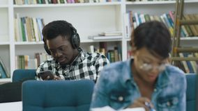 Ελκυστικό αφρικανικό βιβλίο ανάγνωσης γυναικών σπουδαστών στη σύγχρονη βιβλιοθήκη ενώ αφρικανικός άνδρας σπουδαστής που χρησιμοπο απόθεμα βίντεο