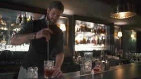 Ελκυστικό γενειοφόρο bartender που αναμιγνύει το ρούμι και τον πάγο στο γυαλί με το μακρύ ραβδί μετάλλων Μπάρμαν που κατασκευάζει απόθεμα βίντεο