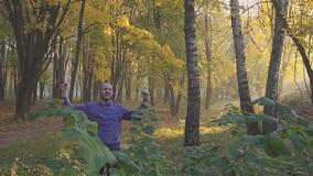 Ελκυστικό εξωτερικό νεαρών άνδρων που στέκεται στα χέρια πάρκων συναισθηματικά που αυξάνονται, συνειδητοποίηση έννοιας της επιτυχ απόθεμα βίντεο
