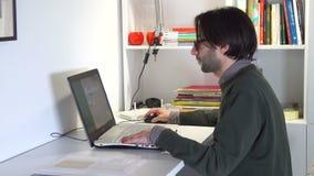 Ελκυστικό επιχειρησιακό άτομο στην περιστασιακή ένδυση που εργάζεται στο lap-top φιλμ μικρού μήκους