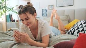 Ελκυστικό ευτυχές και χαμογελασμένο νέο καυκάσιο κορίτσι που και που δακτυλογραφεί στο smartphone στηργμένος στο κρεβάτι απόθεμα βίντεο
