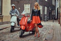 Ελκυστικό ζεύγος, ένα όμορφο άτομο και ένα προκλητικό θηλυκό που στέκονται σε μια παλαιά οδό με δύο αναδρομικά μηχανικά δίκυκλα στοκ φωτογραφία με δικαίωμα ελεύθερης χρήσης