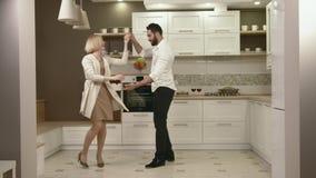 Ελκυστικό ζεύγος που έχει τη διασκέδαση που χορεύει μαζί στην κουζίνα απόθεμα βίντεο