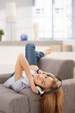 Ελκυστικό θηλυκό που βάζει στη μουσική ακούσματος καναπέδων Στοκ φωτογραφία με δικαίωμα ελεύθερης χρήσης