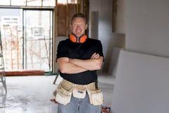 Ελκυστικό και βέβαιο ξυλουργός κατασκευαστών ή άτομο οικοδόμων με την εργασία εργαλείων προστασίας αυτιών ευτυχή στο βιομηχανικό  Στοκ Φωτογραφία