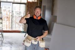 Ελκυστικό και βέβαιο ξυλουργός κατασκευαστών ή άτομο οικοδόμων με την εργασία εργαλείων προστασίας αυτιών ευτυχή στο βιομηχανικό  Στοκ εικόνα με δικαίωμα ελεύθερης χρήσης