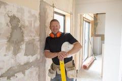Ελκυστικό και βέβαιο ξυλουργός κατασκευαστών ή άτομο οικοδόμων με την εργασία εργαλείων προστασίας αυτιών ευτυχή στο βιομηχανικό  Στοκ φωτογραφίες με δικαίωμα ελεύθερης χρήσης
