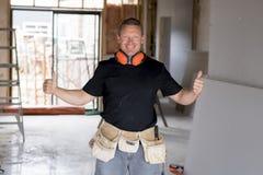 Ελκυστικό και βέβαιο ξυλουργός κατασκευαστών ή άτομο οικοδόμων με την εργασία εργαλείων προστασίας αυτιών ευτυχή στο βιομηχανικό  Στοκ εικόνες με δικαίωμα ελεύθερης χρήσης