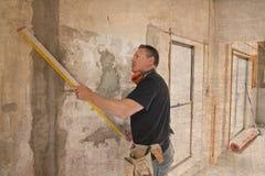 Ελκυστικό και βέβαιο ξυλουργός κατασκευαστών ή άτομο οικοδόμων με την εργασία εργαλείων προστασίας αυτιών ευτυχή στο βιομηχανικό  Στοκ Εικόνες