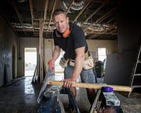 Ελκυστικό και βέβαιο ξυλουργός κατασκευαστών ή άτομο οικοδόμων που απασχολείται στο τέμνον ξύλο με το χειρωνακτικό πριόνι στο βιο στοκ φωτογραφίες με δικαίωμα ελεύθερης χρήσης