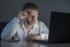 Ελκυστικό και κουρασμένο workaholic άτομο επιχειρηματιών στα γυαλιά που λειτουργούν αργά - νύχτα που χρησιμοποιεί το φορητό προσω στοκ εικόνες