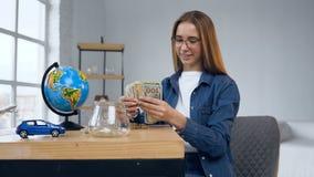 Ελκυστικό καυκάσιο βάζο γυαλιού ανοίγματος γυναικών με τα χρήματα απόθεμα βίντεο