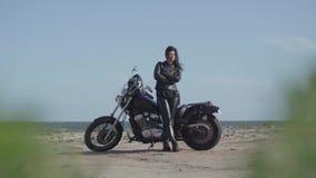 Ελκυστικό καυκάσιο κορίτσι brunette στα ενδύματα δέρματος που στέκονται κοντά στη μοτοσικλέτα στην παραλία της θάλασσας Χόμπι φιλμ μικρού μήκους