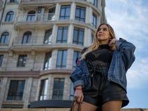 Ελκυστικό κορίτσι με τη ρέοντας τρίχα σε ένα σακάκι τζιν ενάντια στο σκηνικό ενός σύγχρονων κτηρίου και ενός μπλε ουρανού στοκ εικόνες