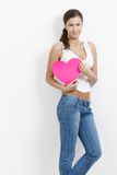 Ελκυστικό κορίτσι με τη ρόδινη καρδιά στο χαμόγελο χεριών Στοκ Εικόνες