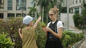 Ελκυστικό κορίτσι με το παιδί που χρησιμοποιεί το κινητό τηλέφωνο για να βρεί μια διεύθυνση απόθεμα βίντεο