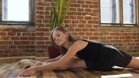 Ελκυστικό κορίτσι που κάνει την τεντώνοντας συνεδρίαση σε ένα πάτωμα Το ελκυστικό νέο ballerina στο μαύρο tutu συμμετέχει στο τέν απόθεμα βίντεο